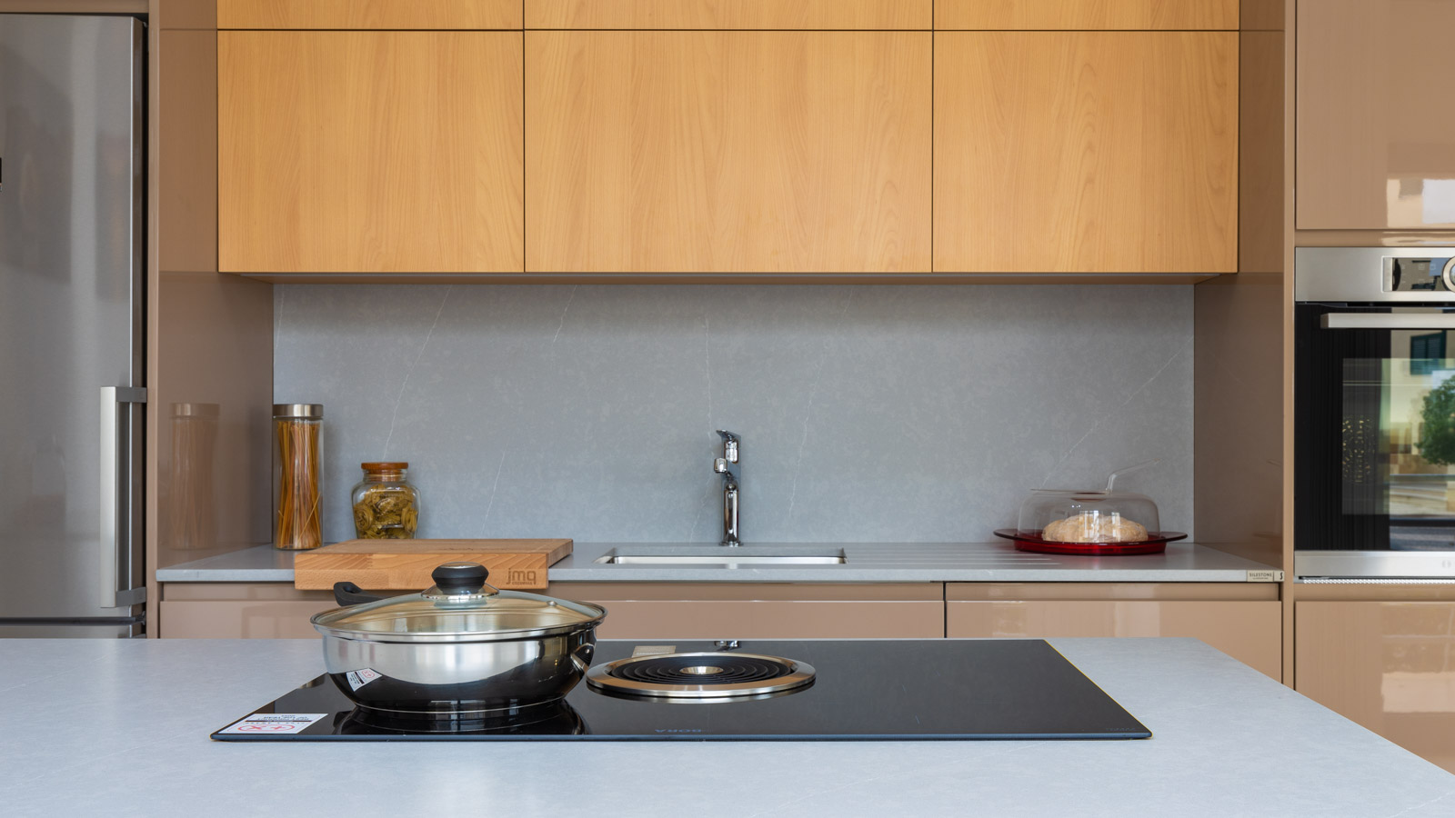 Kitchen in Showroom in Armação de Pêra, with lacquered and melamine fronts. Worktop and splashback Silestone. Peninsula with BORA Basic