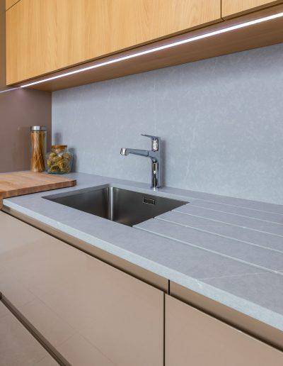 Cozinha moderna com iluminação LED nos móveis superiores e rasgos para escorredor na bancada