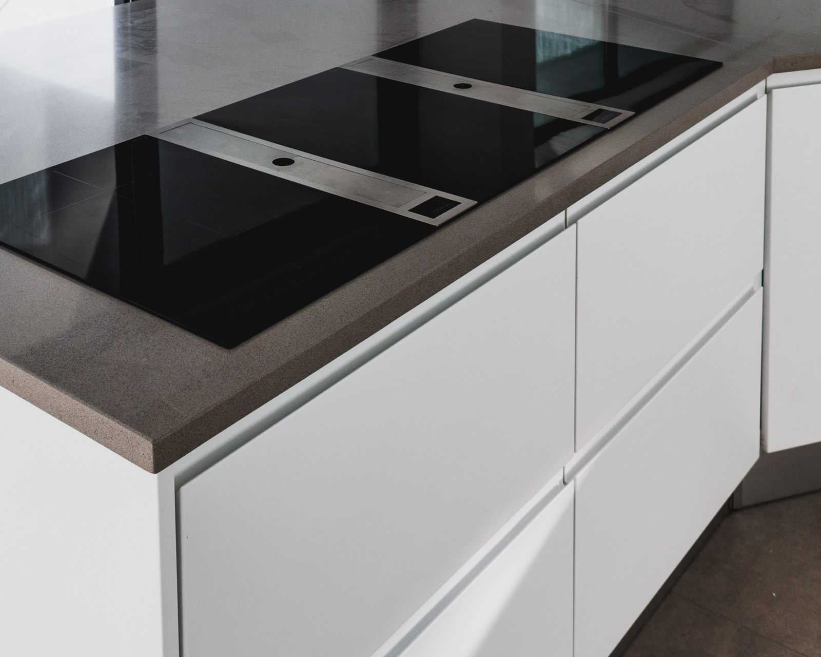Handleless kitchen island, with white matte lacquered fronts and the induction+extraction system BORA Classic