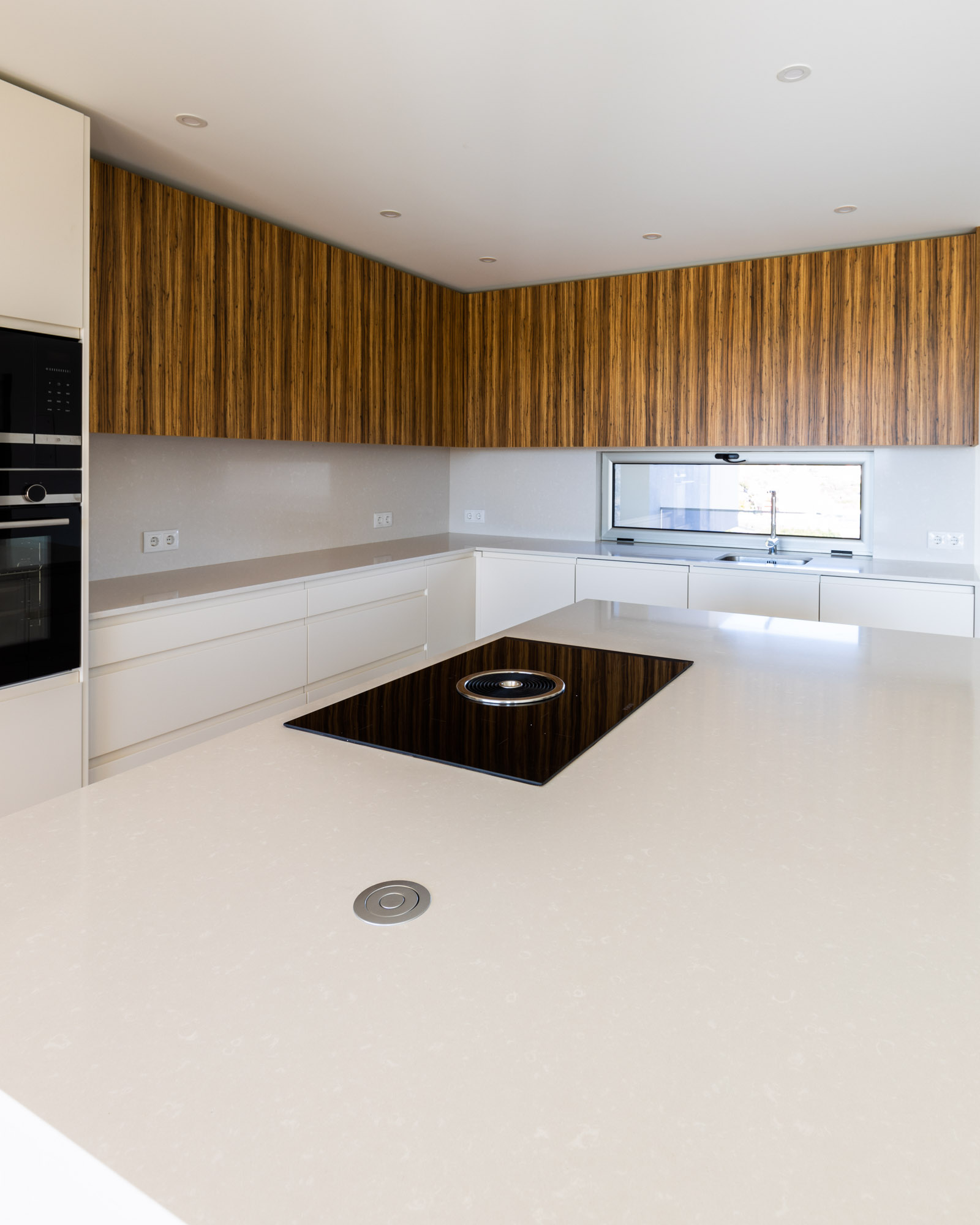 Handleless kitchen with island and white and zebrawood fronts, white worktop and splashback and BORA Basic system