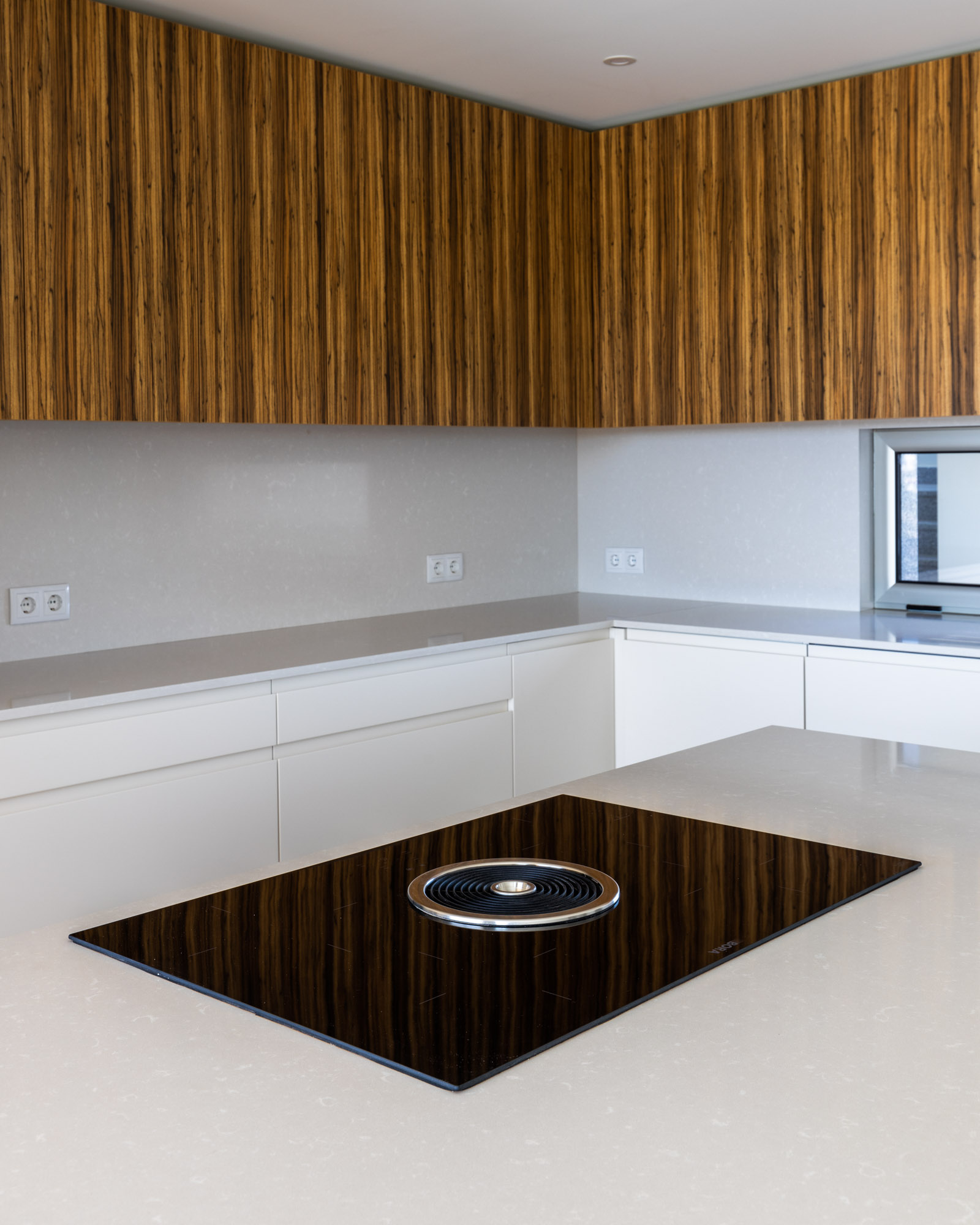 Handleless kitchen with island and white and zebrawood fronts, and BORA Basic system