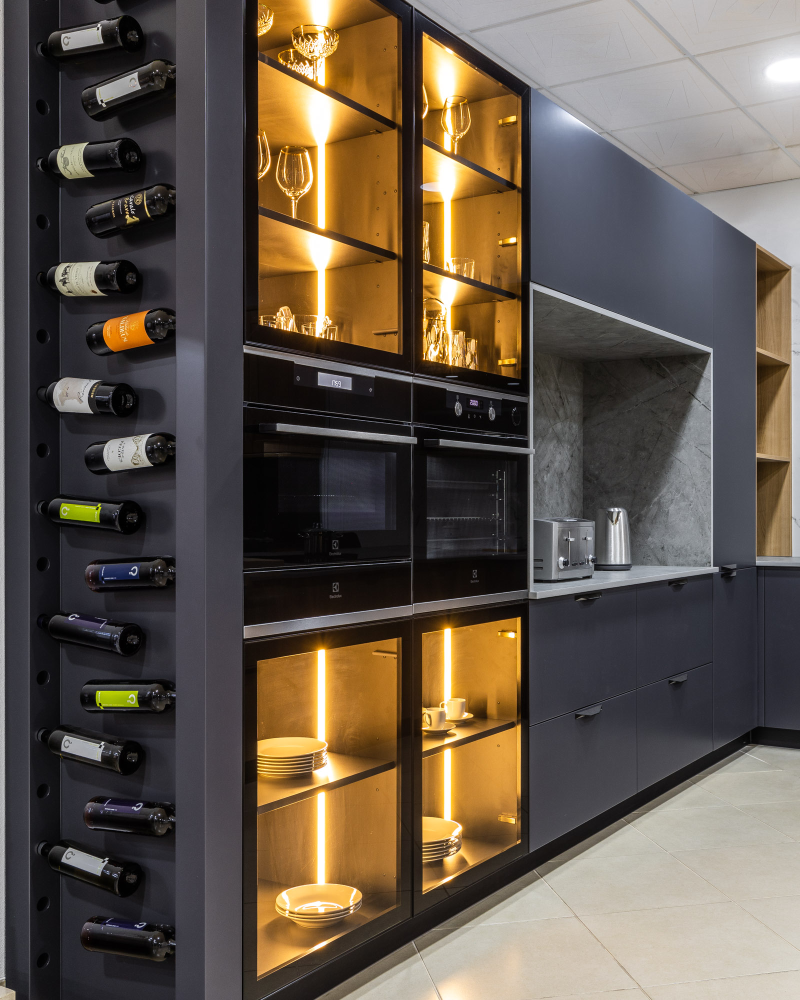 Glass columns with lights and wine rack in kitchen, in JMQ Cozinhas showroom.