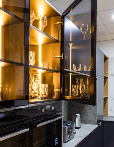 Glass columns with lights in kitchen, in JMQ Cozinhas showroom.