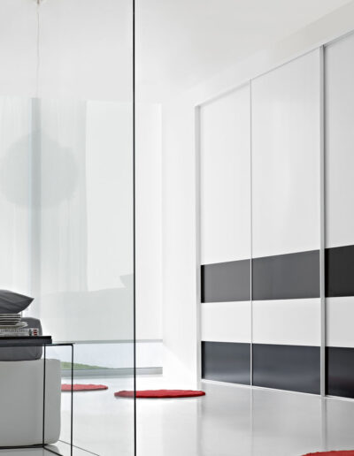 Sliding door closet with black and white lacquered doors.