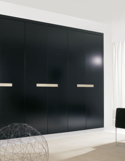 Wardrobe with black lacquered doors with built-in white handler.