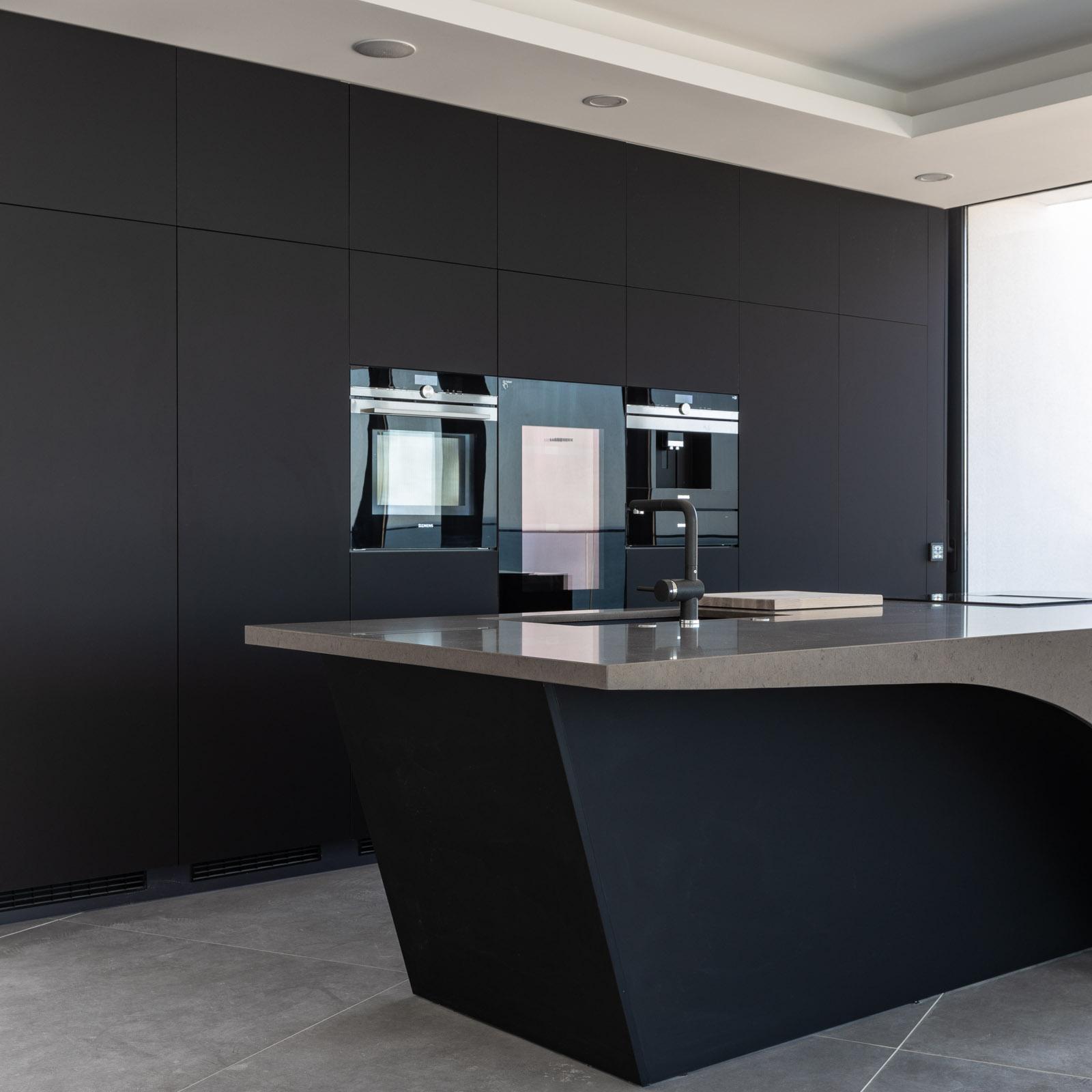 Cozinha moderna com ilha em lacado branco e bancada preta
