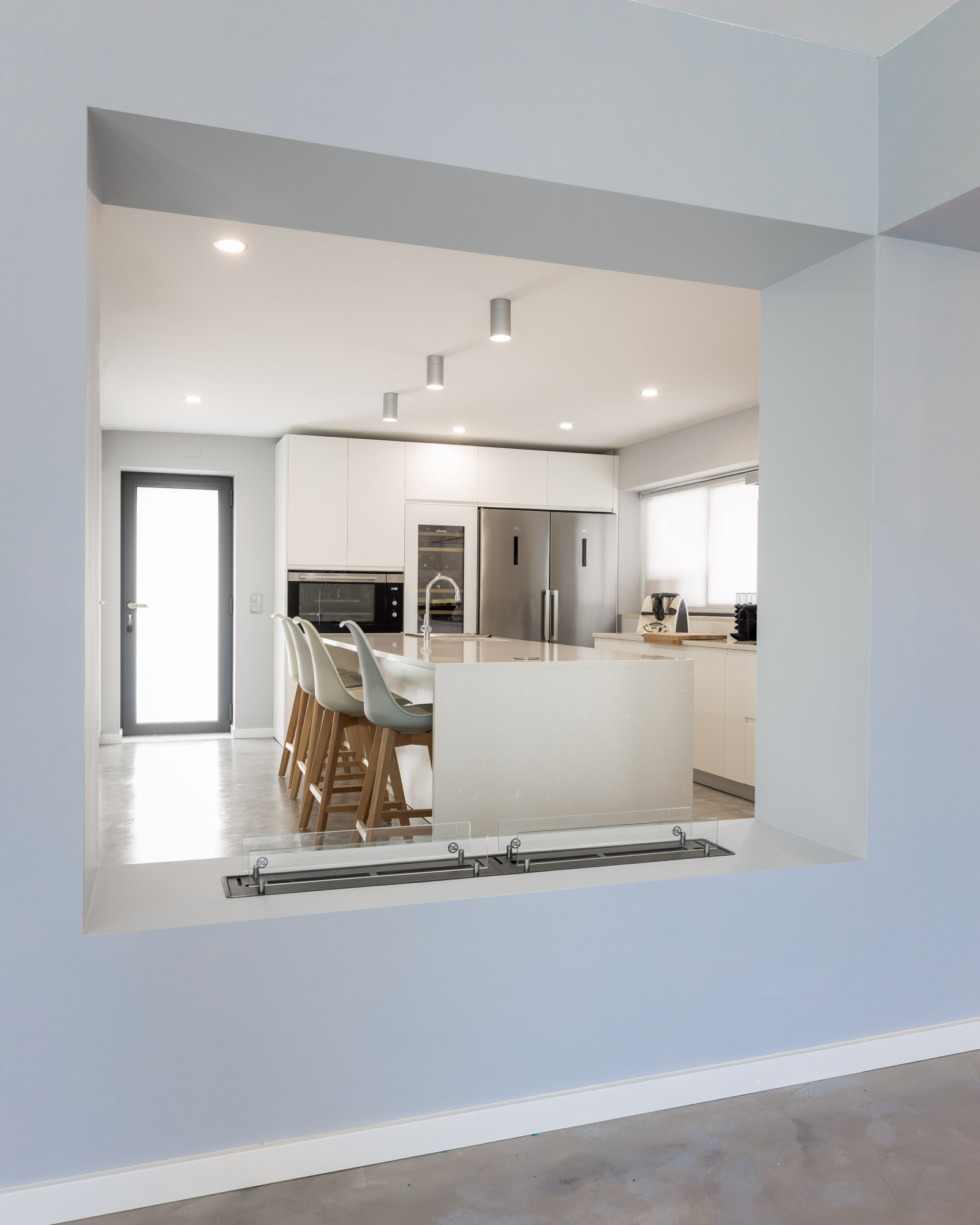 Cozinha moderna com ilha, com frentes em lacado branco mate sem puxadores, com bancada e forro de parede em Silestone, Side by Side AEG, garrafeira Liebherr e forno de 90 cm