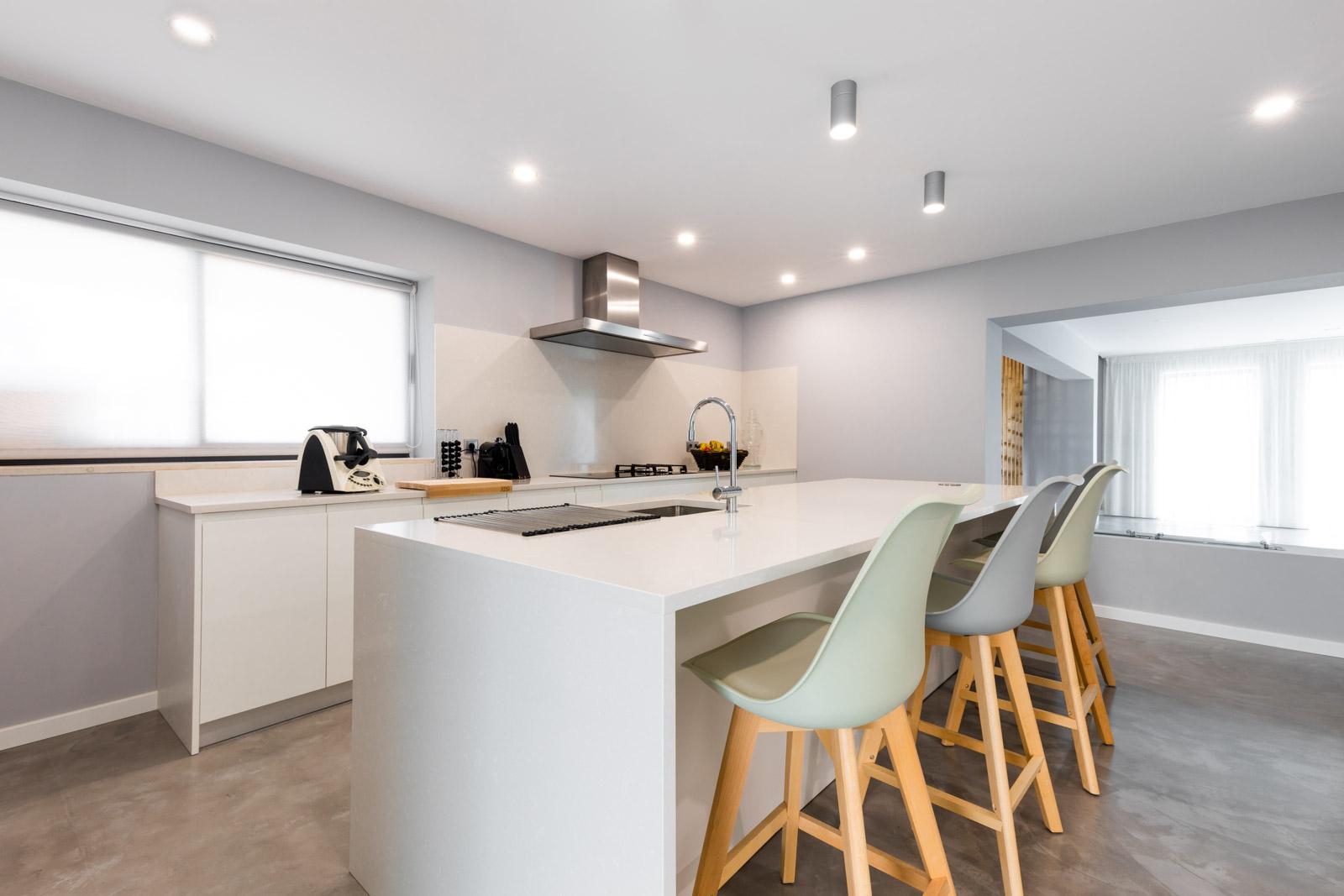 Cozinha moderna com ilha, com frentes em lacado branco mate sem puxadores, com bancada e forro de parede em Silestone Yukon