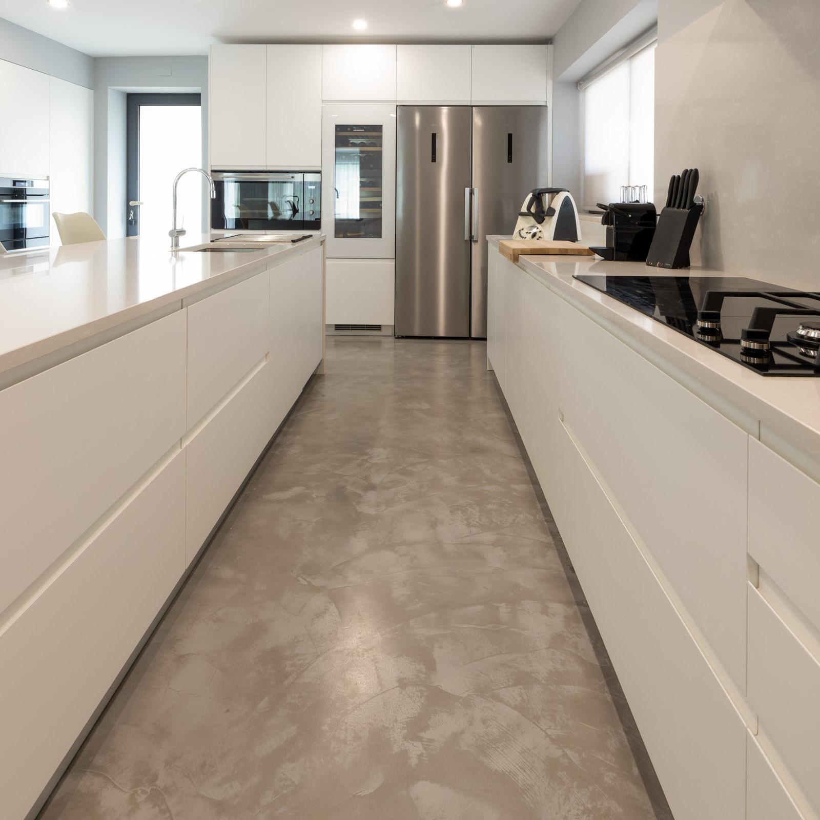 Cozinha moderna com ilha, com frentes em lacado branco mate sem puxadores, com bancada e forro de parede em Silestone Yukon, Side by Side AEG, garrafeira Liebherr e forno de 90 cm