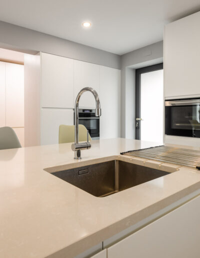Handleless high-end modern kitchen, with white matte lacquered fronts. With worktop and splashback in Silestone, Side by Side, wine cabinet Liebherr and 90-cm oven
