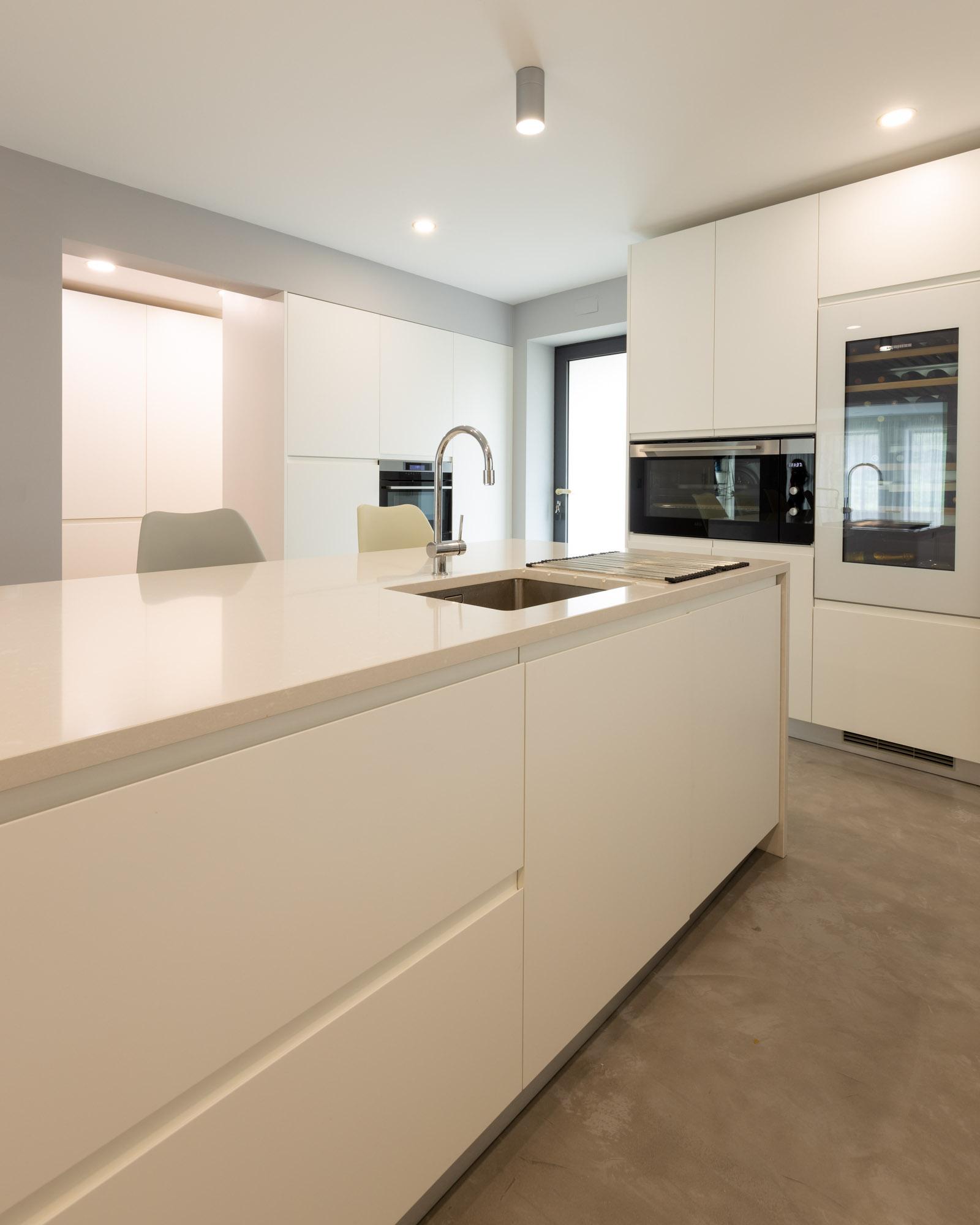 Cozinha moderna com ilha, com frentes em lacado branco mate sem puxadores, com bancada e forro de parede em Silestone Yukon, garrafeira Liebherr e forno de 90 cm