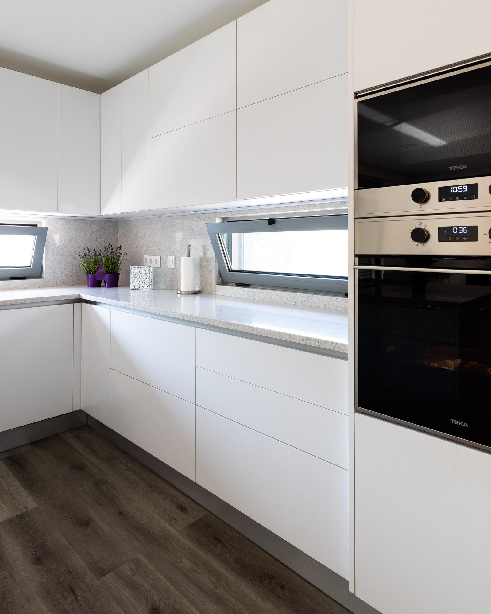 Cozinha branca em termolaminado mate, sem puxadores, com península