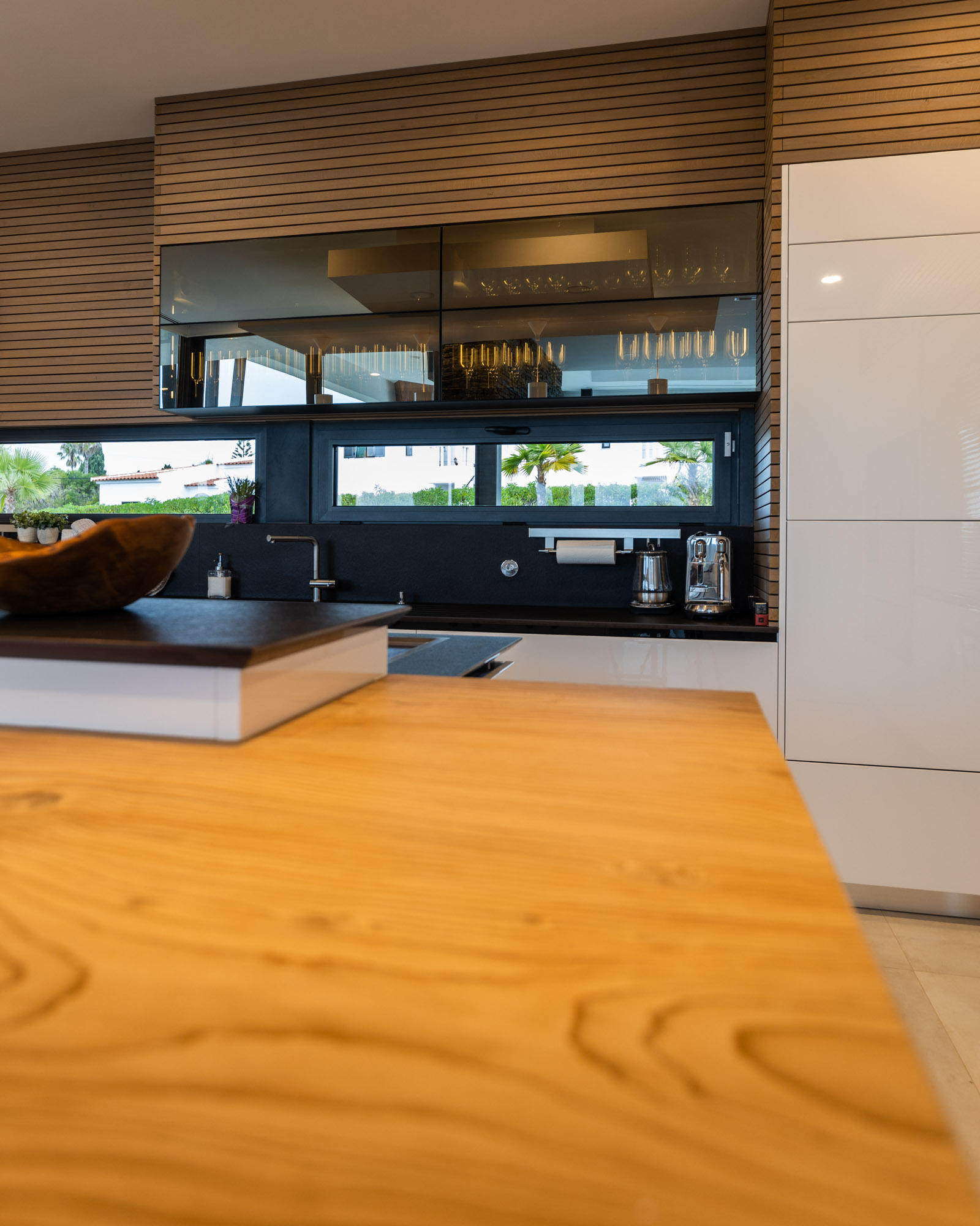 Handleless Modern Kitchen with island, white lacquered fronts and black worktop