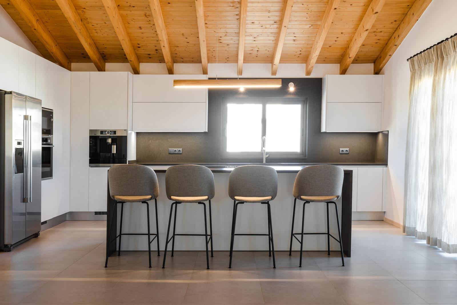 Cozinha moderna em Albufeira em termolaminado branco, com ilha em Silestone Merope Suede, com sistema BORA Classic 2.0 de indução, com combinado Americano, máquina de café, forno e micro-ondas.
