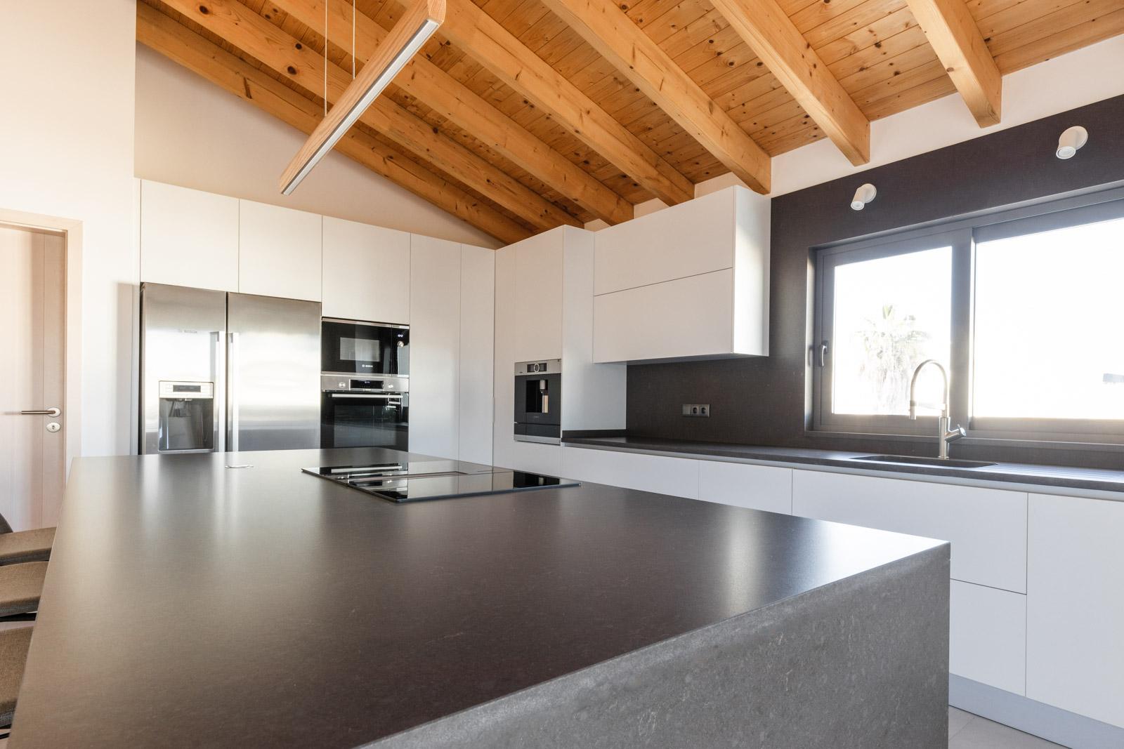 Cozinha moderna em termolaminado branco, com ilha em Silestone Merope Suede, com sistema BORA Classic 2.0 de indução, com combinado Americano, máquina de café, forno e micro-ondas.