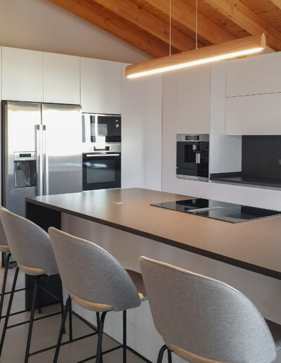 Modern Kitchen with laminate white fronts, worktop and splashback in Silestone Merope Suede, BORA Classic 2.0 induction system, espresso machine, american fridge freezer, oven and microwaves.