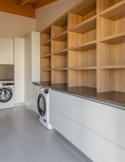 Modern and beautiful laundry in Algarve with washer, dryer and shelves to store clothes.