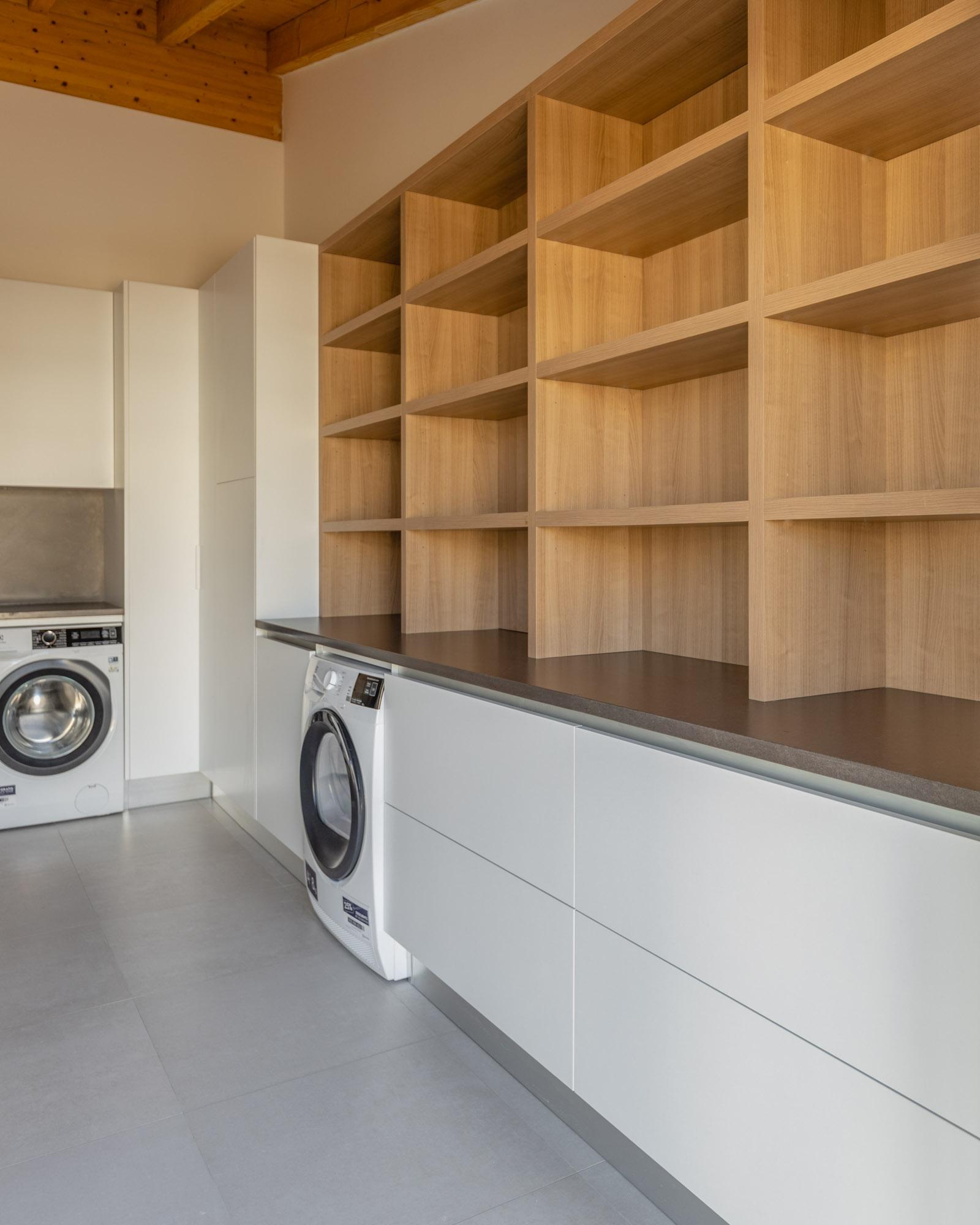 Lavandaria moderna e elegante no Algarve, com máquina de lavar roupa e máquina de secar roupa e prateleiras para arrumação da roupa.