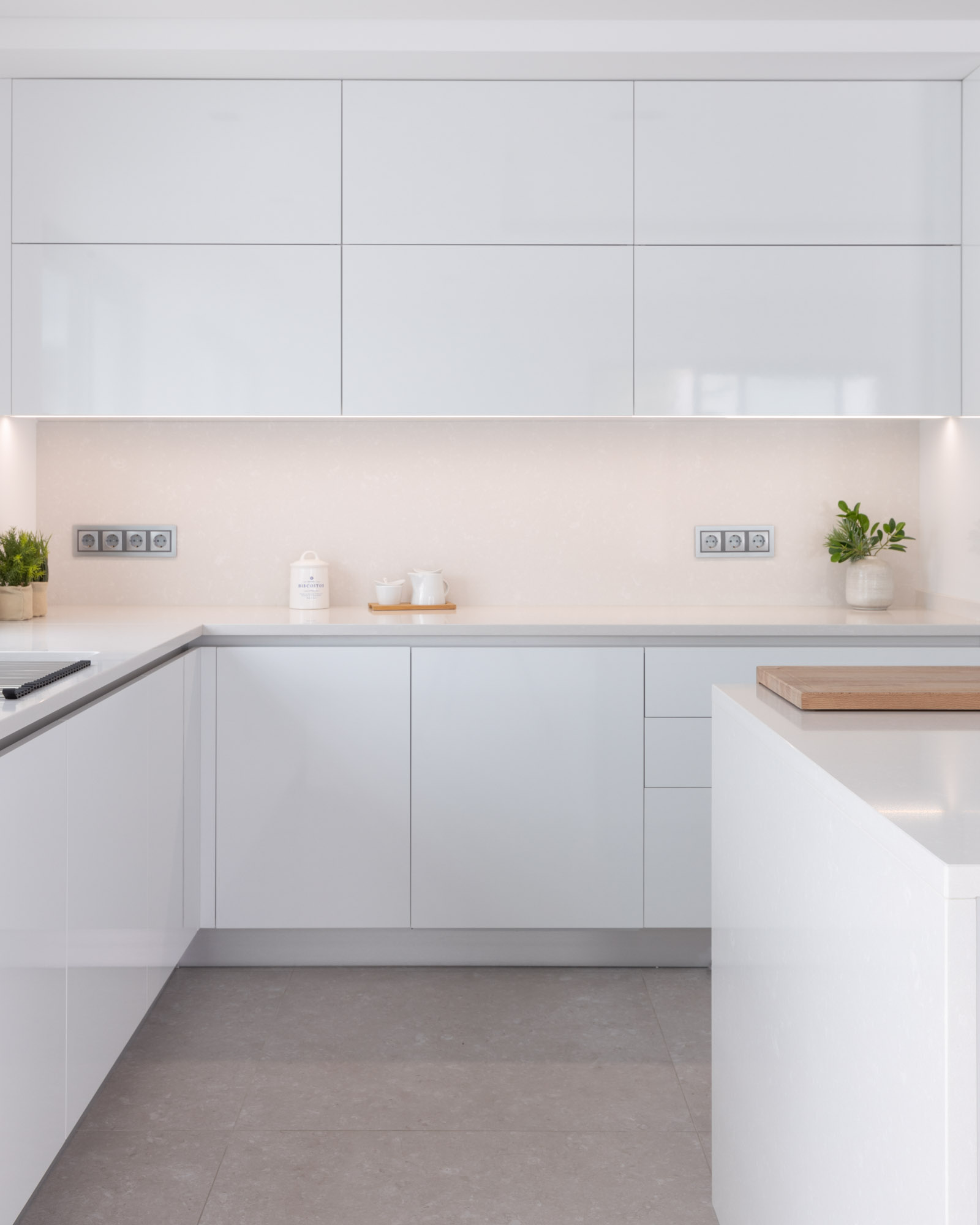 Cozinha em termolaminado branco brilho, com móveis basculantes, bancada e forro de parede em Silestone Yukon