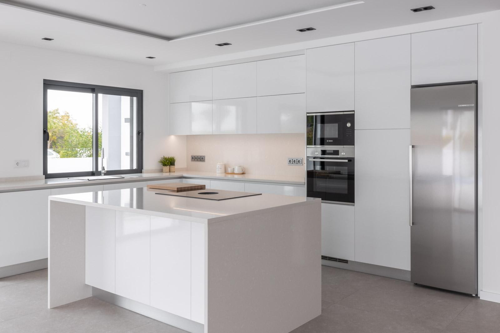 Cozinha com BORA Pure em ilha com Silestone Yukon. Cozinha em termolaminado branco brilho com equipamentos Bosch